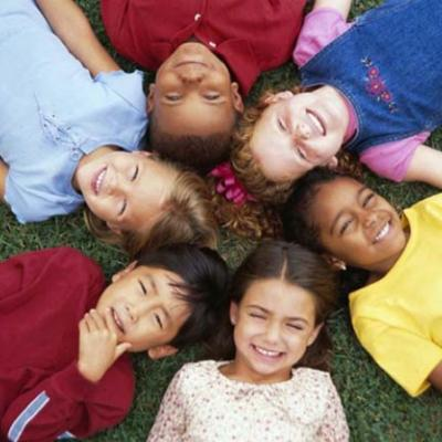 diverse children laying on the grass in a circle looking up at the sky