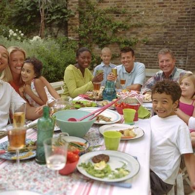 Diverse group of smiling families sitting around a dining table full of food. They are eating a meal together.