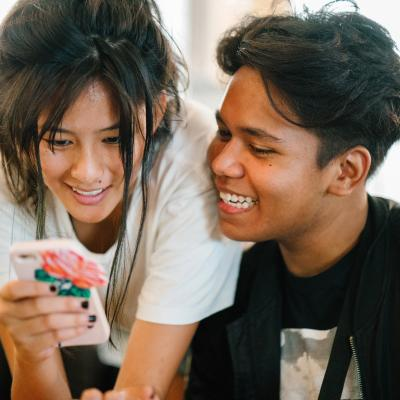 Two adolescents (a boy and a girl) playing on the girl's cell phone