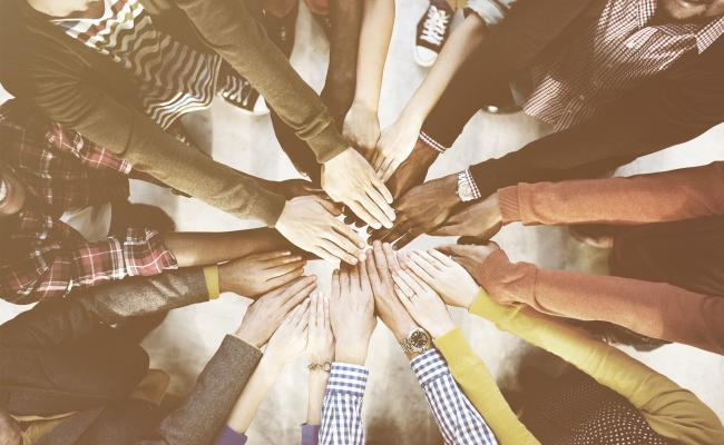 Diverse group of people with hands in a circle
