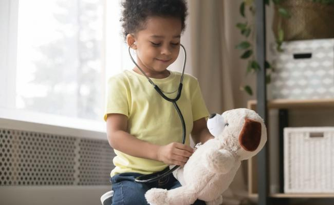 Child playing imaginary doctor with teddy bear