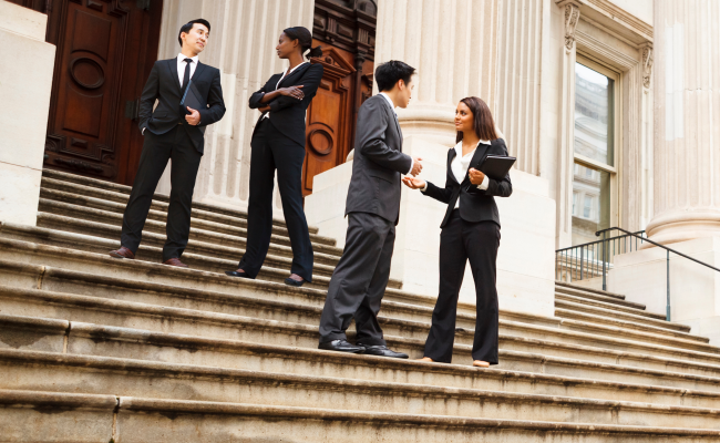 Diverse group of four adults in business suits talking while standing on the steps outside a large white building with large columns. Possibly a courthouse or an official government building.