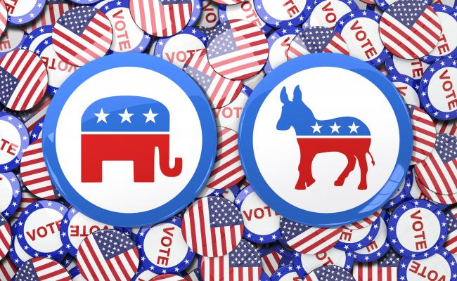 two large election buttons, one with an elephant and the other with a donkey, over a background of smaller buttons with the American flag and the word 'vote' on them